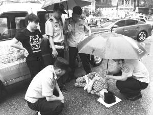 老太太被车撞倒地不起巡逻民警为其撑伞挡雨